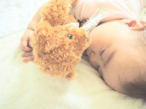 ぬいぐるみと寝る赤ちゃん