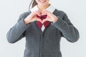 手でハートマークを作る中学生の女の子