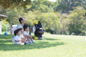 芝生に座る母と子どもたち